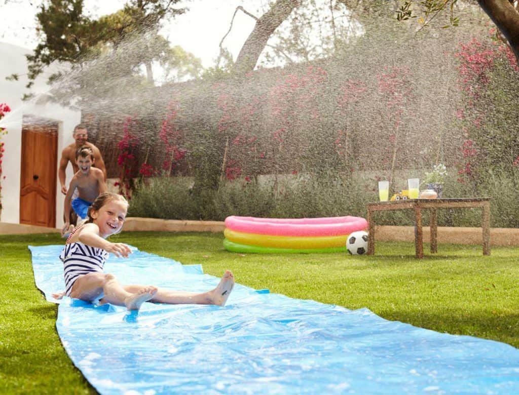 family-sliding-in-lawn